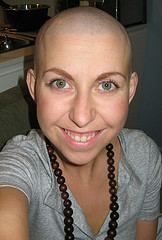 Lady with no hair smiling on cam