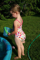 Little girl playing near a kiddie pool
