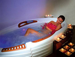 Lady in a white bath tub, lighted candles nearby